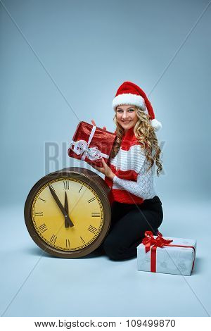 Girl dressed in santa hat holding with a Christmas decorations