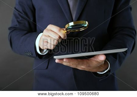 Businessman holding magnifying glass and digital tablet on dark grey background, searching and examining concept