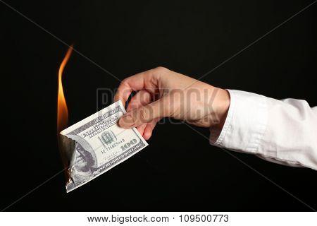 Woman burning dollars on black background