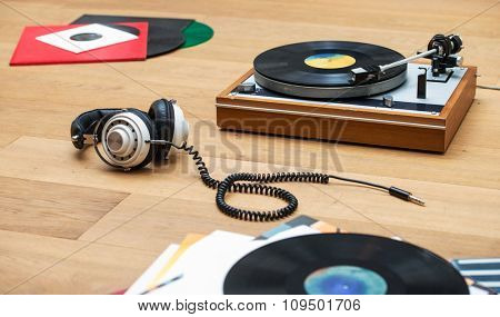 Retro styled image of a record player, vinyl LPs and a head set on a wooden surface