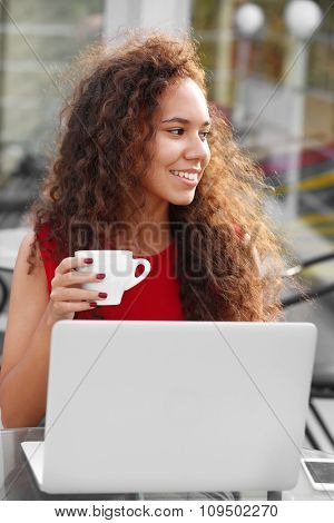 Young pretty business woman in red dress with laptop drinking coffee at summer terrace, close up