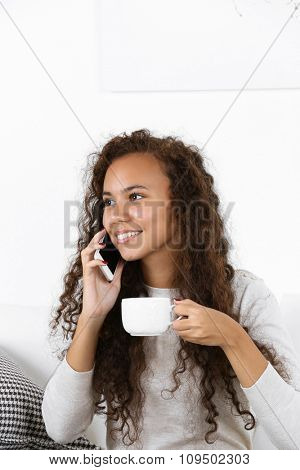 Close up portrait of young woman speaking by cellphone with cup of coffee on white background