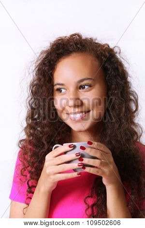 Close up portrait of pretty young woman in pink shirt drinking coffee on white background