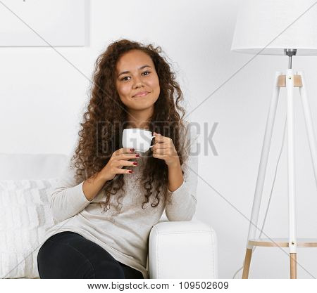 Young woman sitting on comfortable sofa with cup on coffee in hands in white room