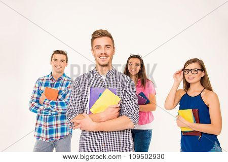 Cheerful Group Of Students Holding Books And Materials