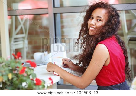 Young smiling pretty woman sitting at the beautiful flowered restaurant's terrace
