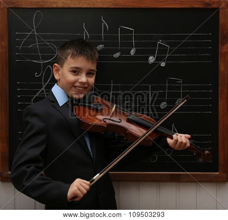 Young cute schoolboy playing the violin the blackboard with musical notes