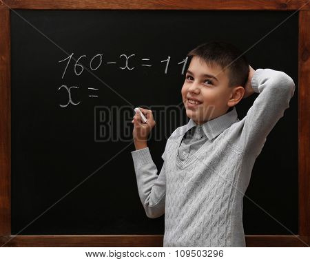 Young cute schoolboy posing at the blackboard
