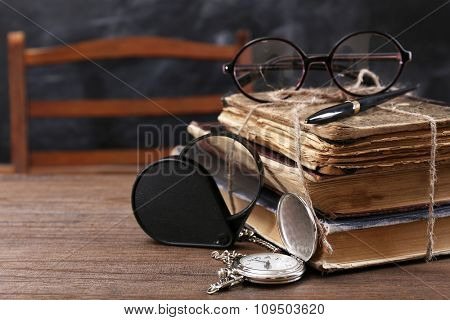 Vintage composition of old books, eyeglasses and magnifying glass on wooden table