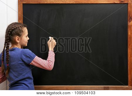 Cute girl posing at the clean blackboard, in the classroom