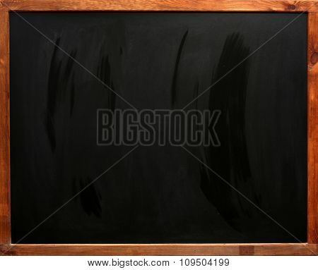 Clean blackboard on white wall, close-up