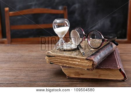 Vintage composition of old books, eyeglasses and hourglass on wooden table