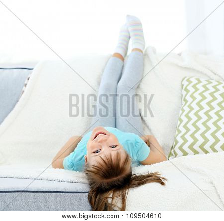 Beautiful little girl lying on sofa, on home interior background