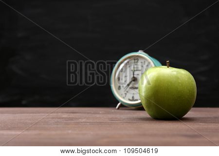 Green apple and clock on blackboard background