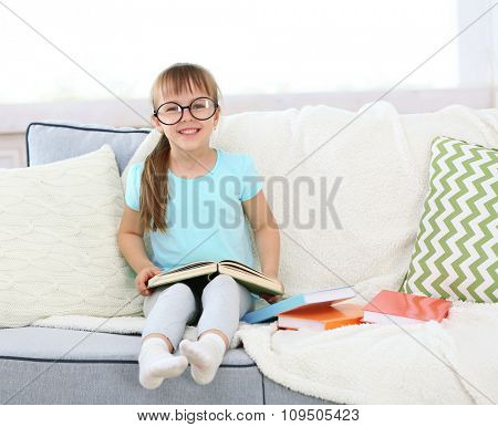 Beautiful little girl sitting on sofa with book, on home interior background
