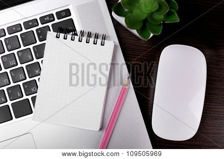 Close-up of comfortable working place on black wooden background, top view