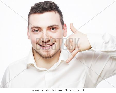 life style  and people concept: young handsome man in shirt gesturing mobile phone near his face and smiling while standing against white background