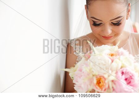 Bride Holding Colorful Bridal Bouquet Next To White Wall