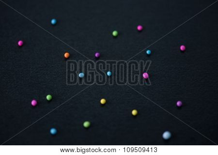 Cute or humorous kind of Christmas background. scattered candy on black paper with slight depth of field.
