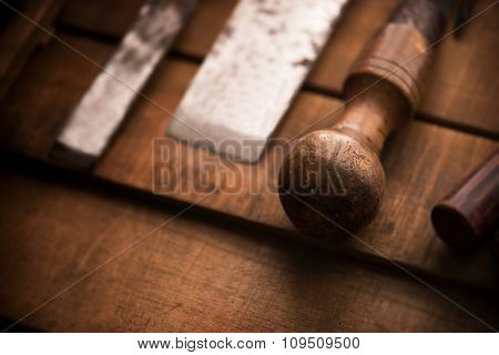 Old and well used wood carving chisels, prepared on a old workbench. Old chisel with an oak handle. Shallow depth of field. Low key.
