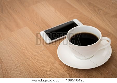 Coffee with smart phone on wood table