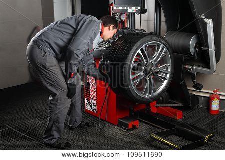 Car Service. The Worker Balances A Tire