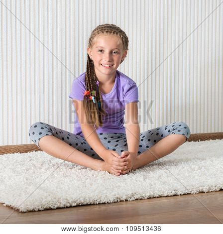 smiling little girl in lilac t-short engaged in fitness