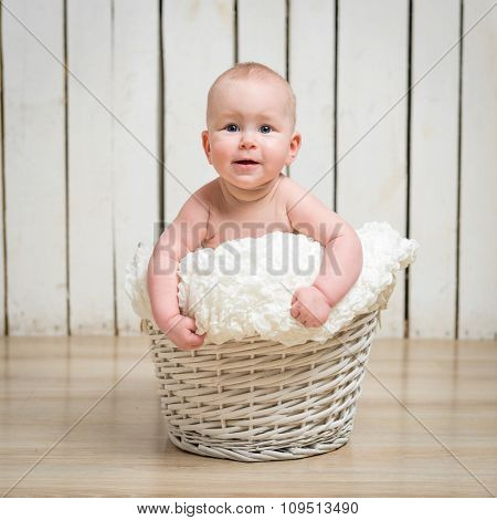 Adorable five month baby girl in wicker basket