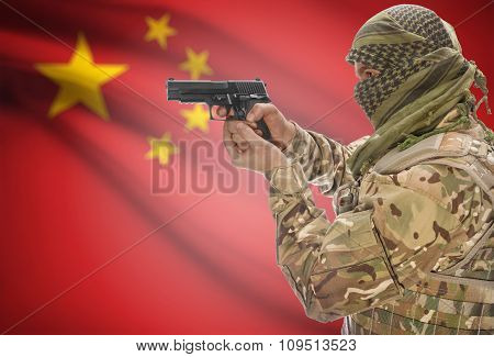 Male In Muslim Keffiyeh With Gun In Hand And National Flag On Background - China
