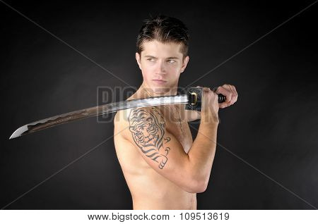 Athletic Man With Sword - Isolated On Dark Background.