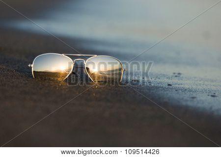 Sunglasses reflect the light of the setting sun at sandy beach