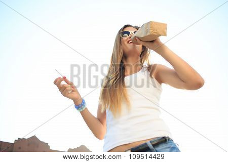 girl drinking from a paper bag in the street. smokes. decadence, anti-social behavior
