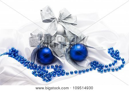 Blue and silver Christmas balls with bows  on white satin fabric
