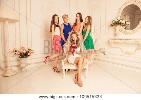 Cheerful Girls Celebrate A Bachelorette Party Of Bride Sitting On A Chair