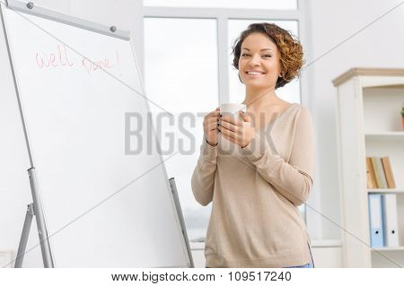 Female employee is drinking coffee by the flipboard.
