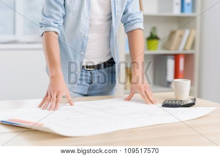 Young workman is standing over the construction plan.