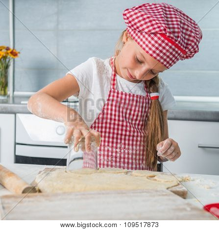 smiling little girl rolling out a dough on a kitchen