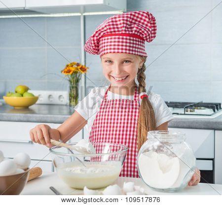 cute little girl adding flour to a dough into a bowl