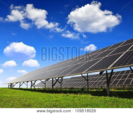 Solar panels against blue sky with clouds.