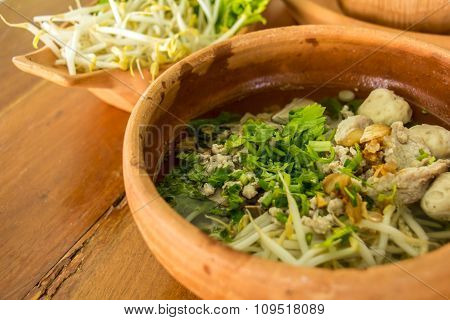 Chicken Soup With Rice, Egg And Noodles In Brown Clay Pot On A Wood  Background For The Menu