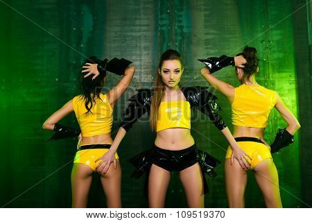 Three Sexy Girls In Stage Yellow Costumes Holding Buttocks