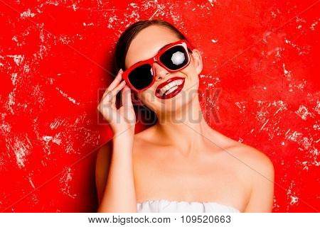 Glamorous Girl Holding The Spectacles Against The Red Background