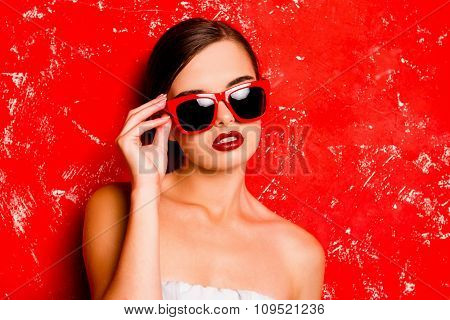 Glamorous Cute Girl With Red Lips Holding The Spectacles Against The Red Background