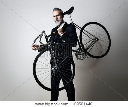 Portrait of a handsome middle aged man wearing suit and holding his classic bicycle on the shoulder.