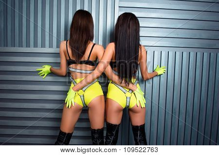 Rear View Of Two Confident Sexy Girls In Stage Costumes