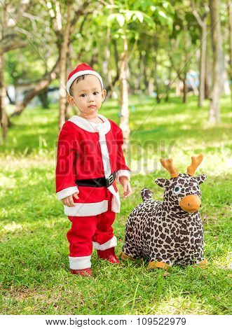 Asian Baby Boy In Santa Claus Suit Is Playing With Reindeer Doll  At The Park