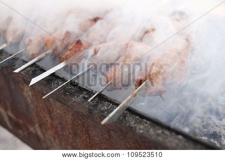 Grilling marinated shashlik on a grill. Shish kebab popular in Eastern, Central Europe and other pla
