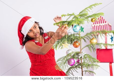 indian girl decorating christmas tree, christmas tree decoration, indian girl with wrapped gifts, is