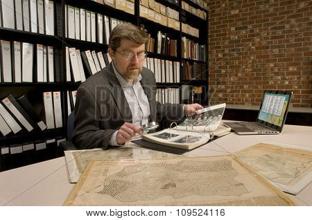 Researcher In Archive, Searching Through Maps And Photographs