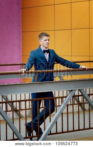 Man In Blue Suit Standing On Bridge.